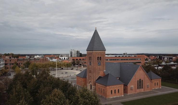 Kirke i forgrund med by i baggrund